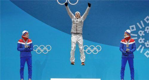 Olympiasieger Andreas Wellinger hebt auch auf dem Podest ab. Robert Johansson (rechts, Bronze) und Johann Andre Forfang (links, Silber), beide Norwegen, applaudieren. Foto  dpa