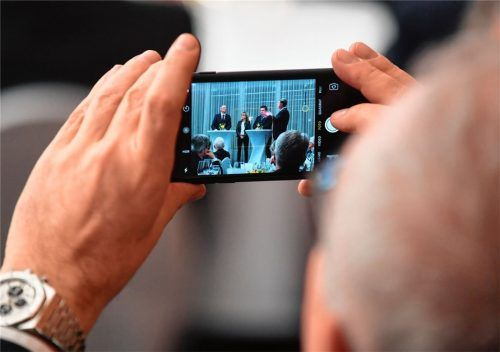 Die Diskussionsrunde im Fokus: Ein ADAC-Gast hält mit seinem Smartphone das Podium im Bild fest. Foto Adac/Klaus Haag