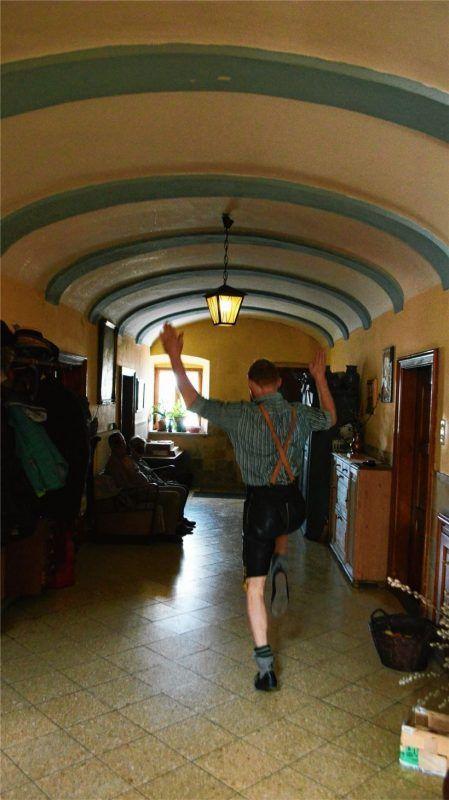 Ein Trachtlerbua stellt – coronakonform – die Plattlerszene von damals in einem Hausflur nach. Dabei beobachten ihn – mit gebührendem Abstand – Verwandte auf der Sitzbank.Fotos  Wastl/RE
