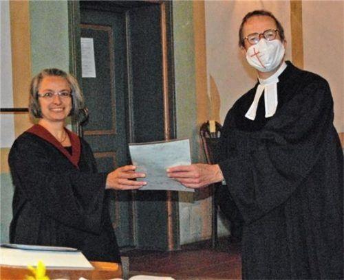 Pfarrer Markus Merz überreicht Irina Müller ihre Ernennungsurkunde. Foto Schlierbach