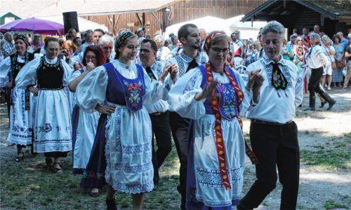 Das Kronenfest der Siebenbürger Sachsen in Waldkraiburg (linkes Bild) zählt zu den Höhepunkten im Jahresverlauf. Dann treten die Volkstanzgruppen auf, und ein junger Bursch besteigt die Krone, einen Baumstamm mit einem prächtigen Blumengebinde (rechtes Bild).Fotos  Siebenbürger Sachsen/Meier