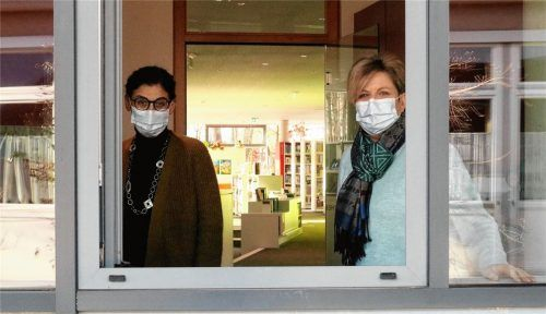 Derzeit hat die Bücherei geschlossen – und so muss ein Blick ins Innere reichen: Andrea Sondhauß (links), stellvertretende Leitung, und Leiterin Gudrun Holzhauser am Fenster. Foto Riediger