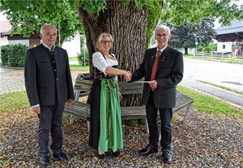 """Am Fuße der alten Linde von Beyharting überreicht Nini Daxenbichler, Vorsitzende des Gartenbauvereins (Mitte), das """"Kuchengeld"""" an Diakon Josef Hilger (rechts) und Kirchenpfleger Jakob Huber (links). Foto  Stache"""