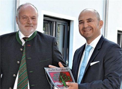 Bürgermeister Thomas Einwang (links) übergibt dem Geschäftsführer des MVZ Buchbach, Dr. Francisco X. Moreano, eine Erinnerungstafel mit dem Buchbacher Wappen.
