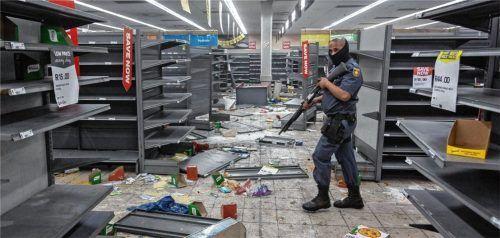 Ein bewaffneter Polizist  steht in einem Laden, der von Plünderern völlig verwüstet worden ist. Die Knappheit an Dingen des täglichen Bedarfs, die durch die Gewalttaten entsteht, trifft vor allem die ärmsten Menschen des Landes. Foto dpa