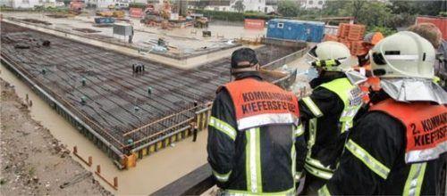 In eigener Sache ausgerückt: Der Kieferbach war in Kiefersfelden über die Ufer getreten und hatte die Baustelle, auf der das neue Feuerwehrhaus entsteht, geflutet. Foto Schmidt