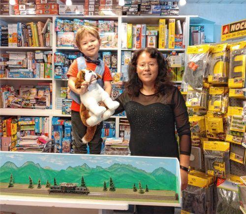 Spielwaren fürs Leben: Händlerin Sabine Schädlich mit ihrem Sohn Thomas in ihrem Priener Laden, vor sich ein selbst gefertigtes Modell zum Testen der Eisenbahn-Spurweiten für ihre Kunden. Foto Sennhenn