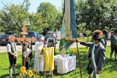 Fähnrich Martin Engelsberger (rechts) bei der Segnung der restaurierten Fahne durch Pater John (Mitte). Foto Strim