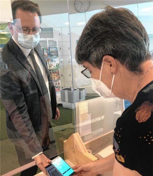 Bad Aiblings Bürgermeister Stephan Schlier macht es vor: In der Bücherei gilt ab sofort die 3G-Regelung. Büchereimitarbeiterin Sibylle Meißner kontrolliert die Impfung.Foto re