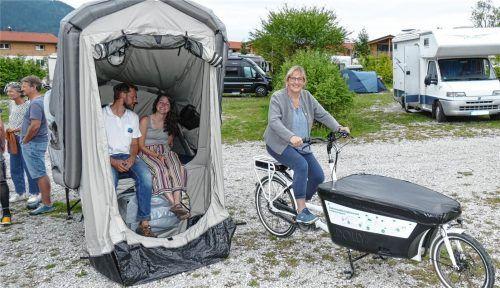 Campingplatz-Betreiberin Julia Egger sitzt gemütlich auf dem E-Bike, mit dem Iris Schreiber (im Zelt) 150 Kilometer weit angereist ist. Neben ihr hatE-Camping-Experte Martin Rolletschek Platz genommen. Foto Wegscheider
