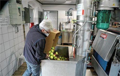 Der Kunde füllt die Äpfel in einen Bottich, dort wird das Obst gereinigt, und wenige Minuten später kommt der Saft heraus.