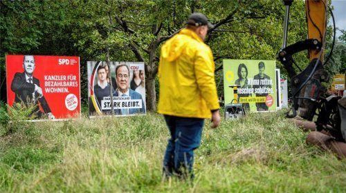 Ein Arbeiter steht am Morgen vor den großflächigen Wahlplakaten für die Bundestagswahl der SPD mit Kanzlerkandidat Olaf Scholz, der CDU mit Kanzlerkandidat Armin Laschet und Bündnis 90/Die Grünen mit Kanzlerkandidatin Annalena Baerbock und Spitzenkandidat Robert Habeck. Foto dpa-Bildfunk