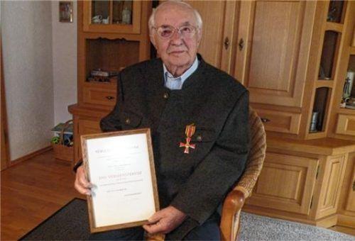 Ernst Baumgartner präsentiert stolz das Bundesverdienstkreuz, das ihm verliehen wurde. Foto Schick