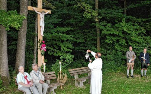 Pater John segnet das renovierte Pestkreuz. Auf der Bank sitzen Peter und Pauline Kaffl.Foto Strim