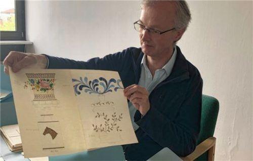 Stadtarchivar Konrad Kern präsentiert eine der Musterzeichnungen, nach deren Vorbild eine Glasvase bemalt wurde.Foto  Grundner