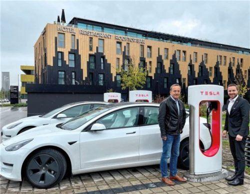 """Gerhard Maier, Geschäftsführer von """"My home my hotel"""" (links), mit stellvertretendem Bürgermeister Daniel Artmann, freuen sich über die Tesla-Ladestationen.Foto Stadt Rosenheim"""
