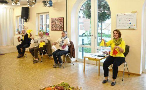 Mit gefalteten Servietten in der Hand tanzen die Senioren und Tanzleiterin Martina Kreisel (rechts) im Bürgerhaus Raubling einen Walzer im Sitzen. Fotos Huber