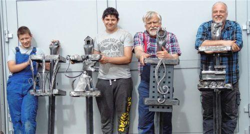 Mit Stolz betrachten (von links) Korbinian Mauder und Justin Karschner sowie die beiden Schmiedemeister Johann Reif und Michael Ertlmeier ihre Werke. Nicht mit auf dem Bild ist Justin Jursch, der dritte Teilnehmer des Projekts.Foto re